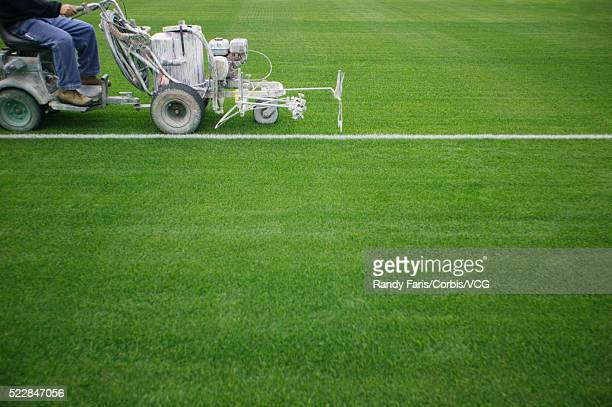 groundskeeper painting white line on athletic field - ground staff stock pictures, royalty-free photos & images