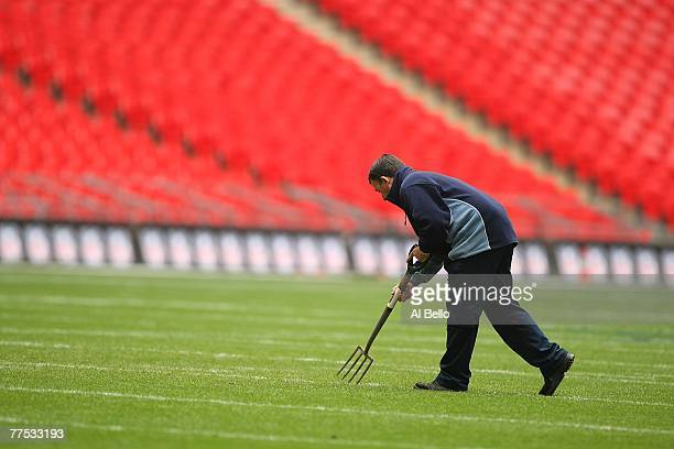 Groundskeeper replaces the divots in the field after practice a day before the game between the Miami Dolphins and the New York Giants on October 27,...