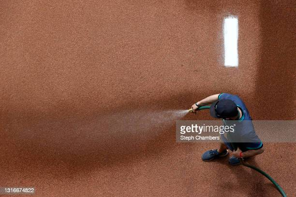Groundskeeper waters the bullpen before the game between the Seattle Mariners and the Baltimore Orioles at T-Mobile Park on May 05, 2021 in Seattle,...
