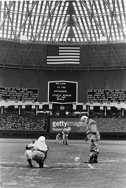 Groundskeepers are forced to wear 'futuristic' spacesuit uniforms as they prepare the diamond for the first game in the Astrodome Houston Texas April...