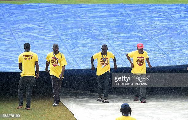 Groundskeepers cover the pitch as rain delayed the match on day four of the Second Test cricket match between India and the West Indies on August 2...