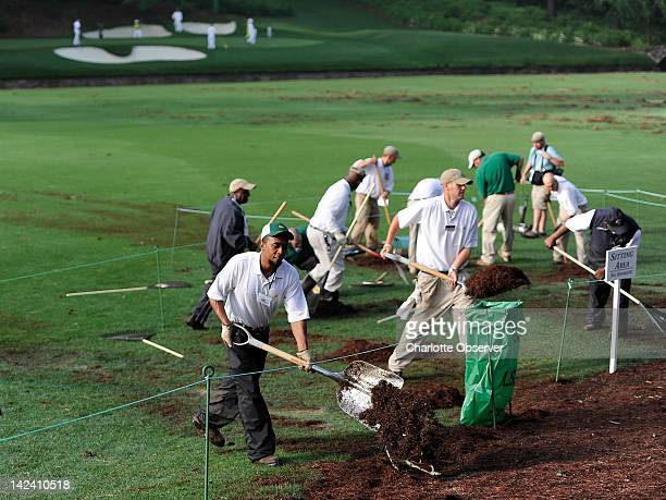 Groundskeepers hurry to clean up debris near Amen Corner at Augusta National Golf Club in Augusta Georgia Wednesday April 4 2012 An overnight storm...