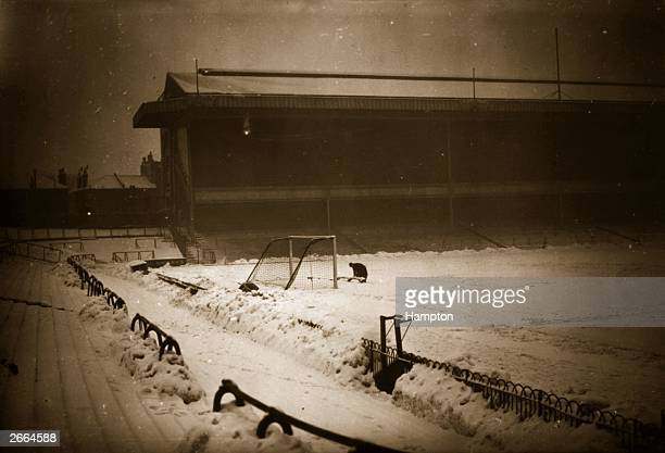 A groundsman attempts to clear the goal area at Arsenal's football pitch at Highbury North London where the days game was cancelled due to a snow...