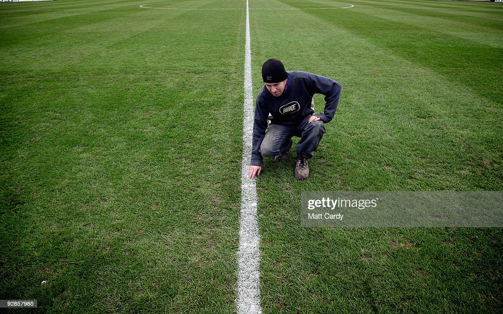 Groundsman Chris Filer examines the freshly painted lines on the pitch at Paulton Rovers Football Club on November 6, 2009 in Paulton, England. Non-league Paulton Rovers are currently preparing for the single biggest day in their 128-year history as they face Norwich City in the FA Cup first round tomorrow. The Somerset village club - which beat Chippenham Town before being drawn against the League One club - normally has an attendance of 200, but will see capacity at the ground swell to 2500 and the match broadcasted live on television to an estimated audience of 2 million.