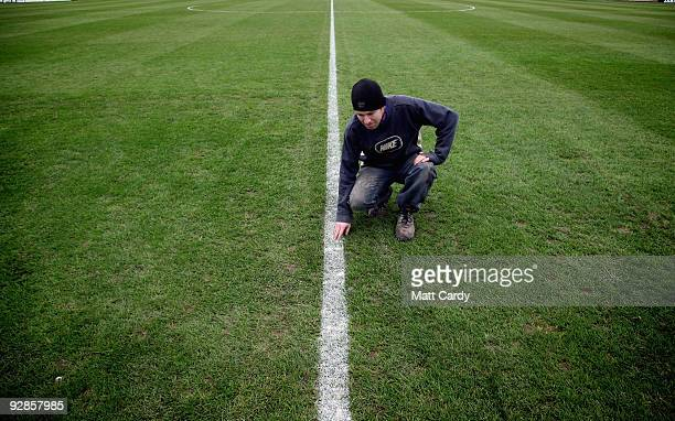 Groundsman Chris Filer examines the freshly painted lines on the pitch at Paulton Rovers Football Club on November 6, 2009 in Paulton, England....