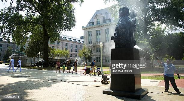 A groundsman cleans off the Indian Warrior Tecumseh statue at Tecumseh Court on the grounds of the US Naval Academy as tourist and cadets pass by in...