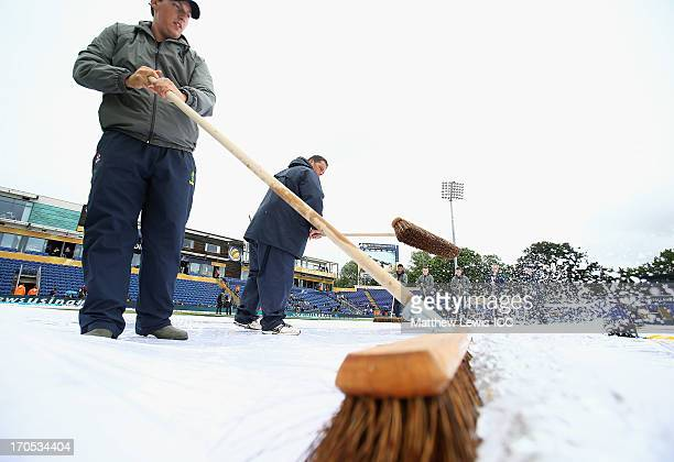 Groundsman clear water off the covers as the match is delayed due to rain ahead of the ICC Champions Trophy Group B match between West Indies and...