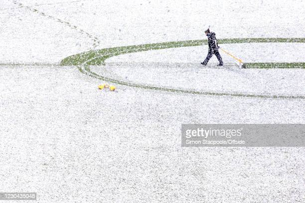 Groundsman clears snow from the pitch before the Premier League match between West Bromwich Albion and Arsenal at The Hawthorns on January 2, 2021 in...