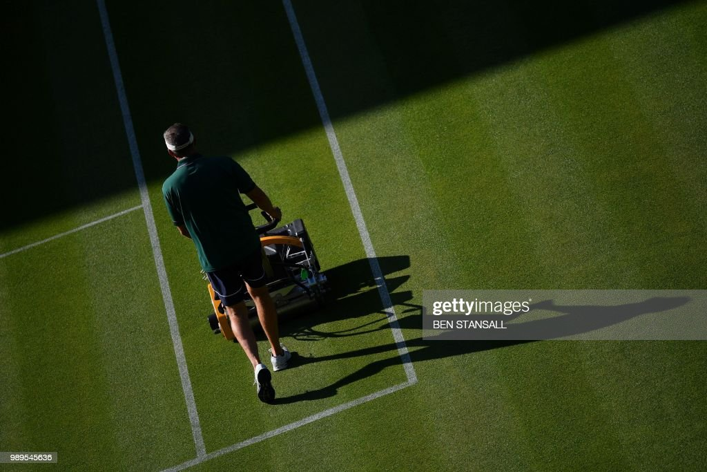 A groundsman cuts the grass on Centre Court at The All England Tennis Club in Wimbledon, southwest London, on July 2, 2018, on the first day of the 2018 Wimbledon Championships tennis tournament. (Photo by Ben STANSALL / AFP) / RESTRICTED