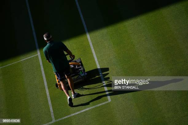 A groundsman cuts the grass on Centre Court at The All England Tennis Club in Wimbledon southwest London on July 2 on the first day of the 2018...