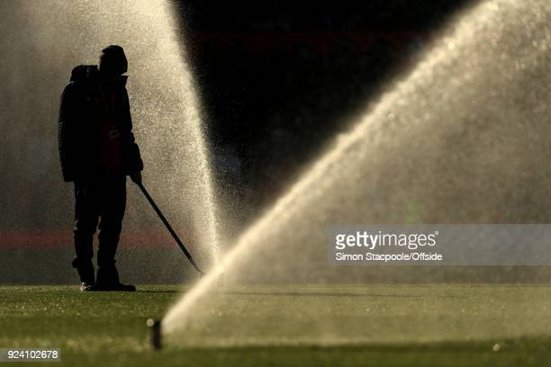 A groundsman is silhouetted against the water sprinklers at halftime during the Premier League match between Manchester United and Chelsea at Old...