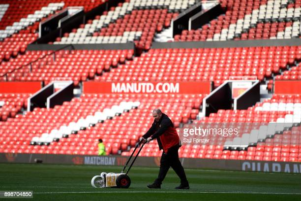 Groundsman marks out the pitch after rain had washed away some of the markings ahead of the Premier League match between Manchester United and...