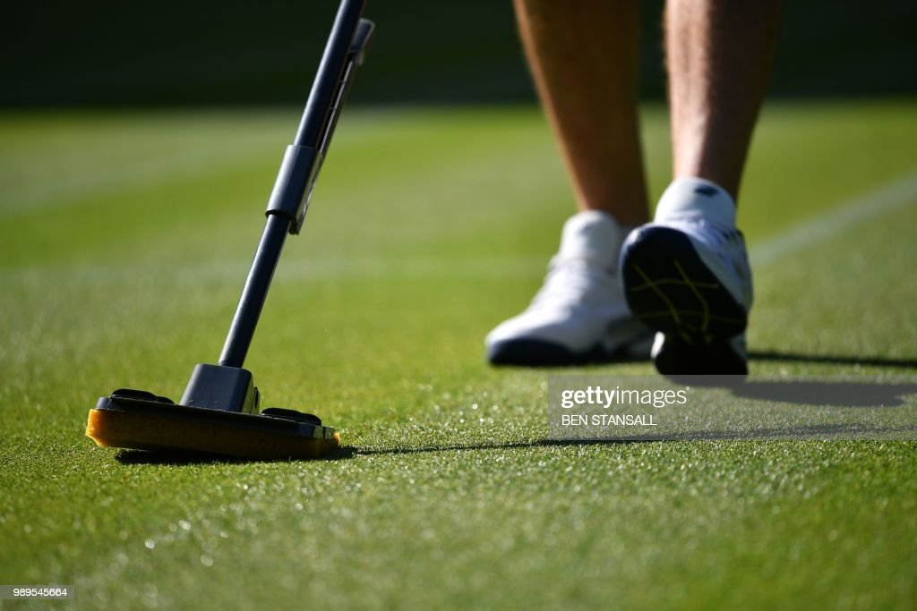 A groundsman mops the court on Centre Court at The All England Tennis Club in Wimbledon, southwest London, on July 2, 2018, on the first day of the 2018 Wimbledon Championships tennis tournament. (Photo by Ben STANSALL / AFP) / RESTRICTED