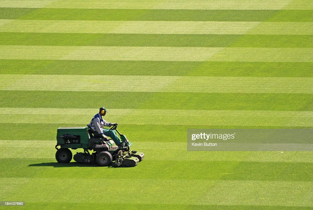 CONTENT] Groundsman mowing the grass using a ride on mower, preparing the sports field (football/soccer pitch).