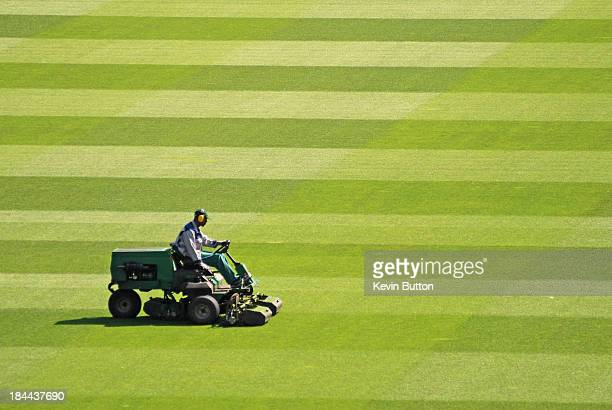 CONTENT] Groundsman mowing the grass using a ride on mower preparing the sports field