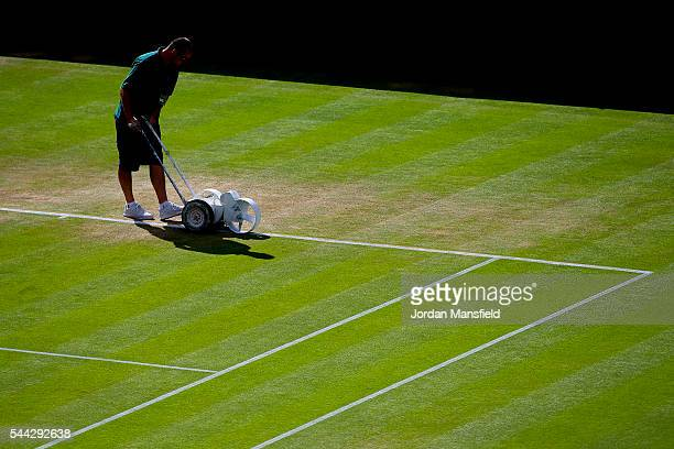 A groundsman paints a line on Centre Court ahead of the start of play on day seven of the Wimbledon Lawn Tennis Championships at the All England Lawn...