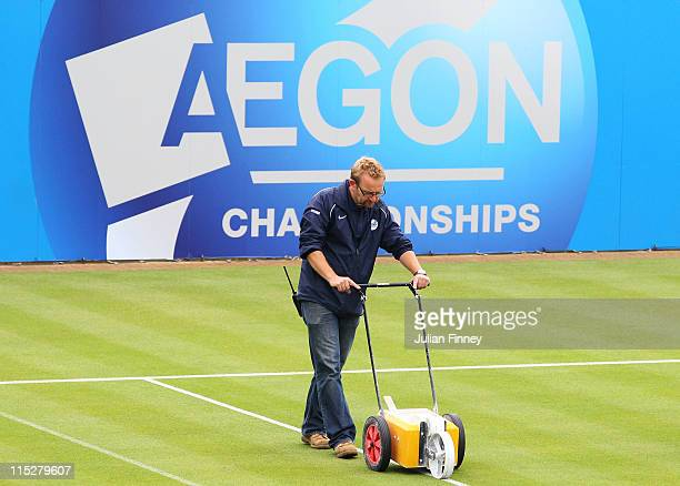 A groundsman paints the court lines as play is delayed by rain on day one of the AEGON Championships at Queens Club on June 6 2011 in London England