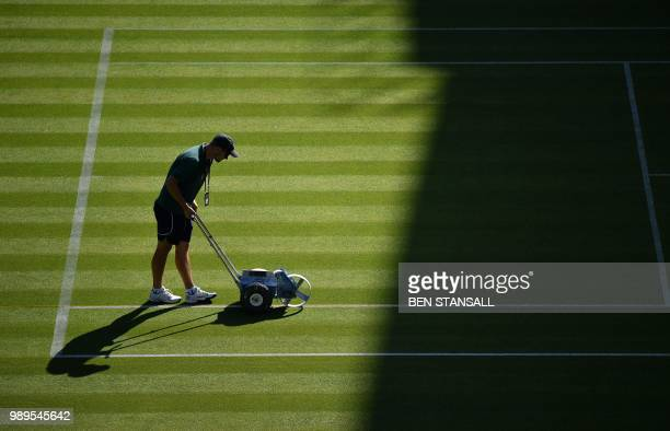 A groundsman paints the lines on the court on Centre Court at The All England Tennis Club in Wimbledon southwest London on July 2 on the first day of...