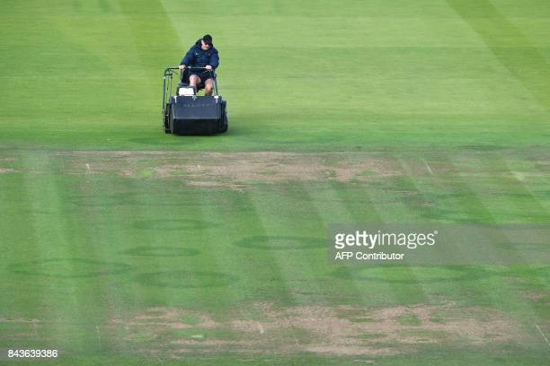 A groundsman prepares the pitch prior to the start of the third international test match between England and West Indies at Lords cricket ground in...