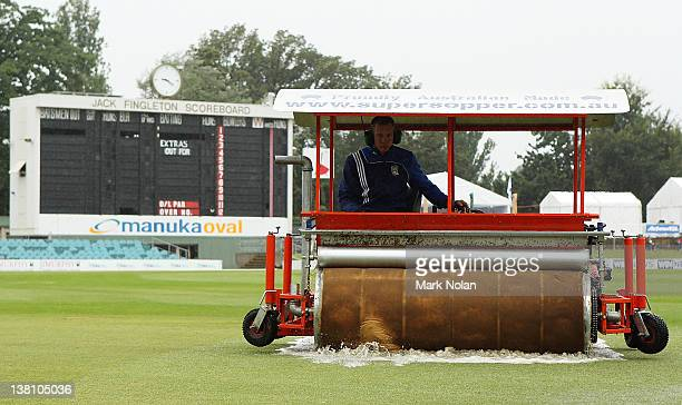 A groundsman removes surface water from the field during the International Tour Match between the Prime Minister's XI and Sri Lanka at Manuka Oval on...