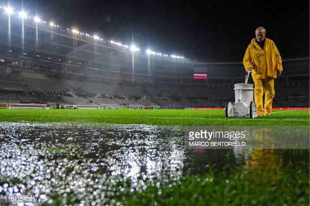 A groundsman repaints the white lines on the pitch after heavy rainfall prior to the Italian Serie A football match Torino vs Inter Milan on November...