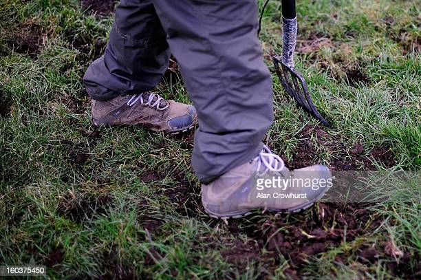 A groundsman repairs the heavy going on the landing side of a fence at Ludlow racecourse on January 30 2013 in Ludlow England