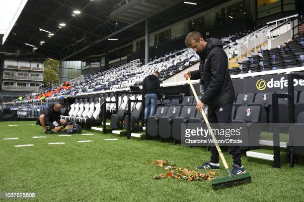 A groundsman sweeps leaves out of the dugouts ahead of the Premier League match between Fulham FC and Watford FC at Craven Cottage on September 22...