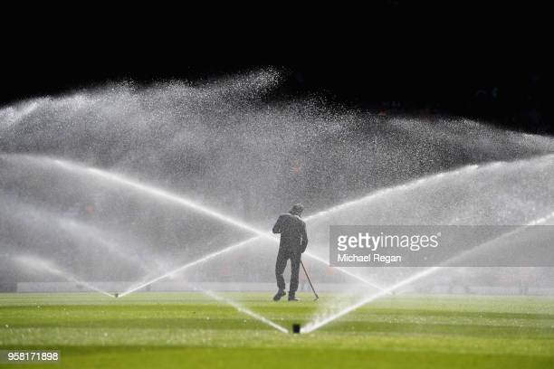 A groundsman tends to the pitch at half time during the Premier League match between Liverpool and Brighton and Hove Albion at Anfield on May 13 2018...