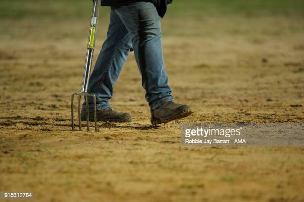 A groundsman tends to the sand on the pitch prior to The Emirates FA Cup Fourth Round Replay at Spotland Stadium on February 6 2018 in Rochdale...