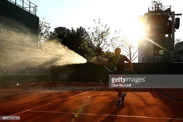 A groundsman waters court ten after the days play on day six of the 2016 French Open at Roland Garros on May 27 2016 in Paris France