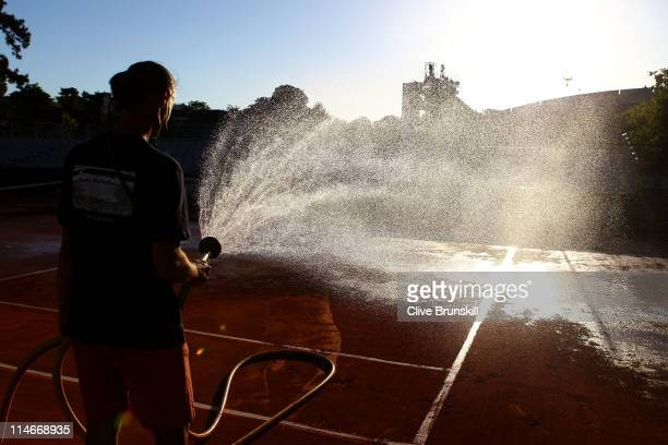 A groundsman waters the court after play on day four of the French Open at Roland Garros on May 25 2011 in Paris France