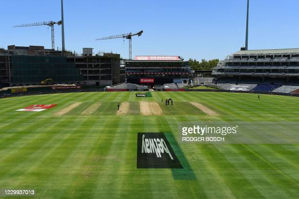 Groundsmen are seen on the empty field at Newlands stadium in Cape Town, South Africa, on December 4, 2020. - The first one-day international cricket...