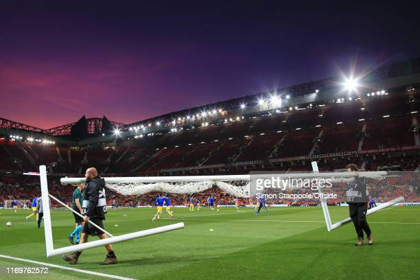Groundsmen carry the practice goal away at sunset ahead of the UEFA Europa League group L match between Manchester United and FK Astana at Old...