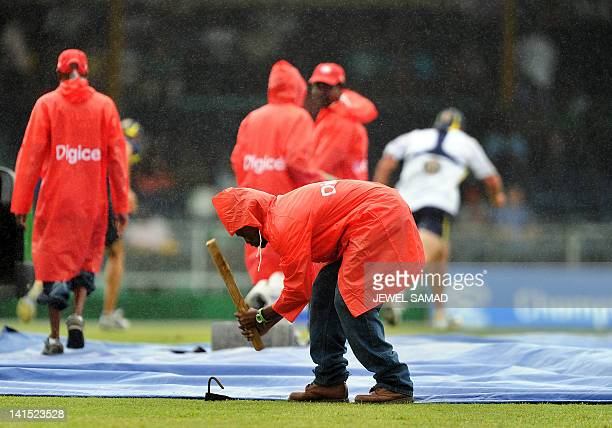 Groundsmen cover the pitch as rain delays the second-of-five One Day International matches between West Indies and Australia at the Arnos Vale Ground...