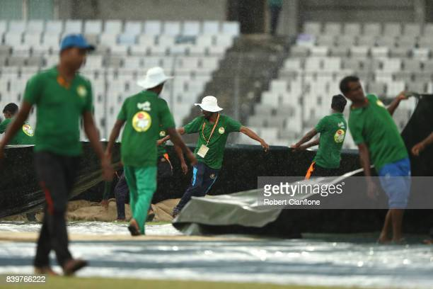 Groundsmen cover the pitch as rain stops play during day one of the First Test match between Bangladesh and Australia at Shere Bangla National...