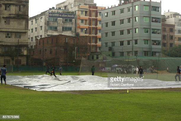 Groundsmen cover the practice wicket as rain falls during an Australian Test team nets session at SherE Bangla National Cricket Stadium on August 23...
