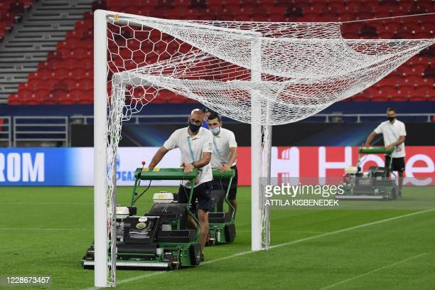 Groundsmen cut the grass after a training sesion on the eve of the UEFA Super Cup football match between FC Bayern Munich and Sevilla FC in Budapest,...