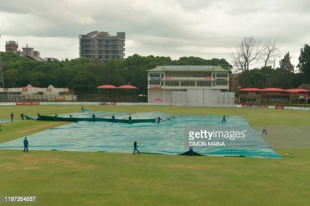 Groundsmen drag a sail onto the field to cover the pitch as rain has delayed play during the third day of the second Test cricket match between...