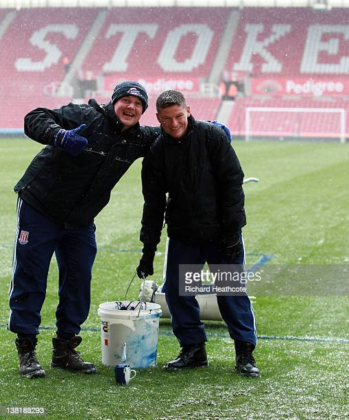 Groundsmen paint the lines blue as snow starts to fall ahead of the Barclays Premier League match between Stoke City and Sunderland at the Britannia...