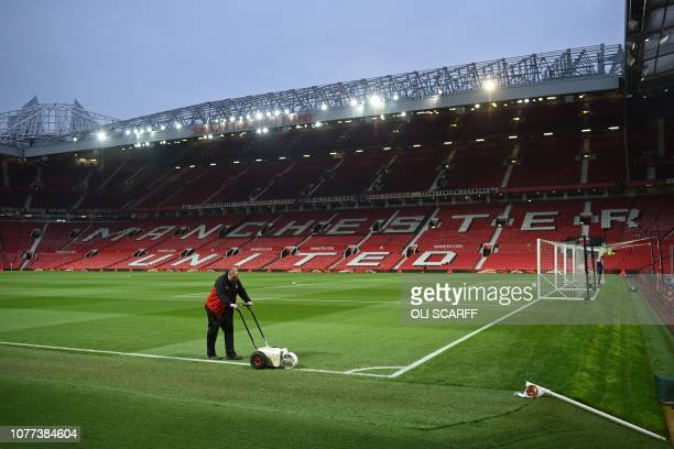 A groundsmen paints the lines as preparations are completed ahead of the English FA Cup third round football match between Manchester United and...