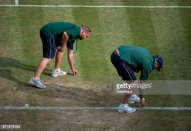 Groundsmen pick up loose pieces of grass on centre court on day five of the Wimbledon Lawn Tennis Championships at the All England Lawn Tennis and...