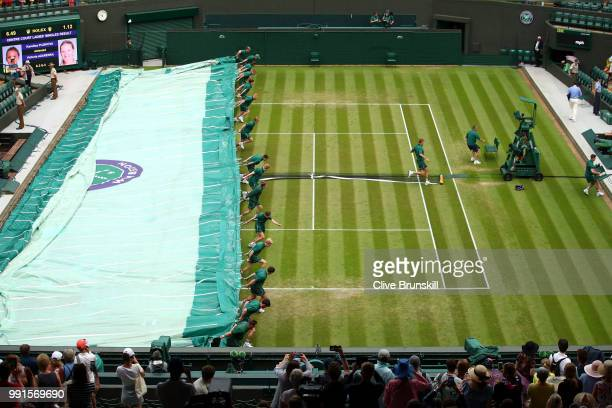 Groundsmen pull covers over the court as rain stops play on day three of the Wimbledon Lawn Tennis Championships at All England Lawn Tennis and...