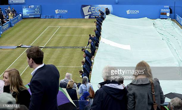 Groundsmen pull the covers across the court as rain delays the start of play between Britain's Andy Murray against Croatia's Marin Cilic during their...