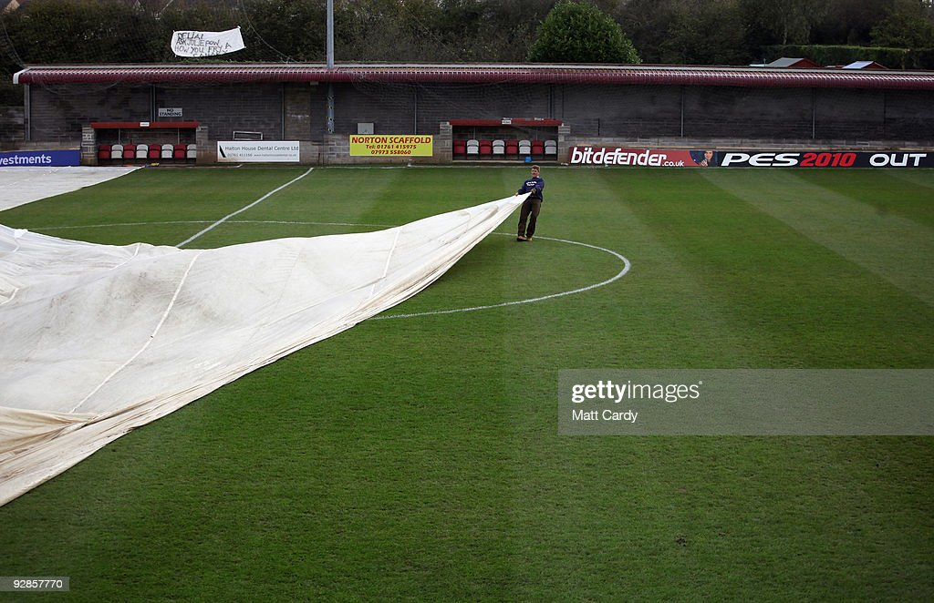 Groundsmen pull the covers over the pitch to protect it from rain at Paulton Rovers Football Club on November 6, 2009 in Paulton, England. Non-league Paulton Rovers are currently preparing for the single biggest day in their 128-year history as they face Norwich City in the FA Cup first round tomorrow. The Somerset village club, which beat Chippenham Town before being drawn against the League One club, normally has an attendance of 200, but will see capacity at the ground swell to 2500 and the match broadcasted live on television to an estimated audience of 2 million.