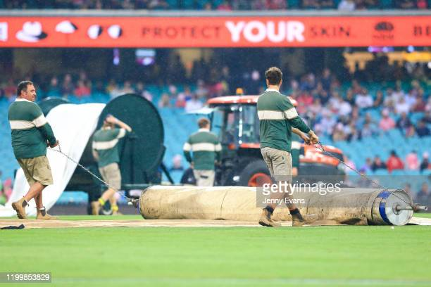 Groundsmen put the covers down after play is stopped due to rain during the Big Bash League match between the Sydney Sixers and the Hobart Hurricanes...
