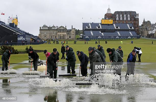 Groundsmen sweep water into the Swilcan Burn from the 1st fairway after heavy rain make the course unplayable early on the second day of the 2015...