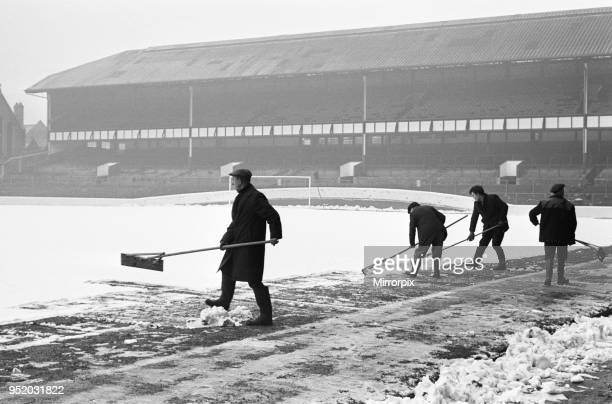 Groundsmen try to clear the snow from the pitch at Goodison Park home ground of Everton Football Club two days before their match against Bristol...