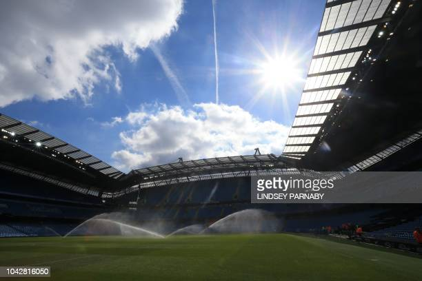 Groundsmen water the pitch peioe to the English Premier League football match between Manchester City and Brighton and Hove Albion at the Etihad...