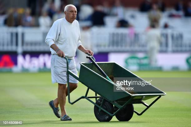 A groundsmen wheels a wheelbarrow filled with sawdust on the field on the second day of the second Test cricket match between England and India at...