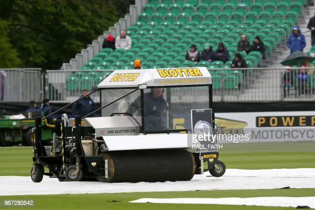 Groundsmen work on the wet pitch at Malahide cricket club in Dublin as the start of play is delayed on the first day of the Test match between...